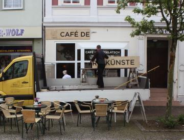 René Bartl beim Anbringen des neuen Projekt-Café Schilds